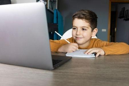 Child taking notes laptop